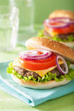 Burger with beef patty cheese lettuce onion tomato Stock Image