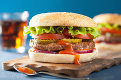 Burger with beef patty lettuce onion tomato ketchup.  Stock Images