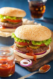 Burger with beef patty lettuce onion tomato ketchup.  Stock Photo