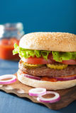 Burger with beef patty lettuce onion tomato ketchup Royalty Free Stock Photos