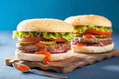 Burger with beef patty lettuce onion tomato ketchup Royalty Free Stock Images