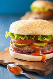 Burger with beef patty lettuce onion tomato ketchup Royalty Free Stock Photo