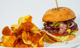 Burger with beef patty tomato onion and potato chips Royalty Free Stock Photography