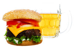 Burger and beer. Big Juicy cheese burger with a beer in the background stock images