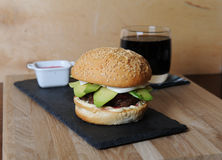 Burger, beer and berry sauce in white gravy boat on a slate base, glass and cutlery served on a wooden board, Stock Image