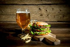 Burger with beer in a glass and fries. On wooden background royalty free stock images