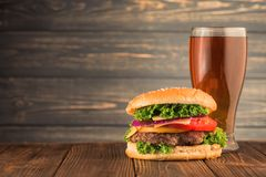 Burger and beer. Tasty big burger and beer glass on wood table Royalty Free Stock Photo