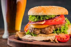 Burger and beer. Tasty big burger and beer glass on wood table Royalty Free Stock Images