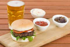 Burger & Beer. Burger in a white bun with summer leaf and tomato served with ketchup caramelised onions, coleslaw and beer. Rustic outdoors setting royalty free stock photo