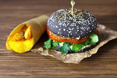 Burger with the black bun, on the kraft paper with fried potatoes on brown wooden background Stock Photo