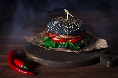 Burger with the black bun, on the kraft paper and red chilli pepper on the dark brown wooden table. Smoke on the Royalty Free Stock Image