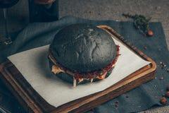 Burger. Black burger on wood background. Russia, Yekaterinburg royalty free stock image