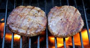 Burger brutzelnd auf dem Grill Stockfoto