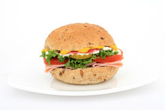 Burger bun sandwich on a plate. Brown whole grain food isolated on white, macro with copy space, lettuce, tomato and ham Royalty Free Stock Photos