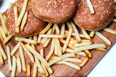 Burger buns with french fries on wooden background. Tasty burger buns with french fries on a wooden background Royalty Free Stock Photo