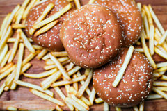 Burger buns with french fries on wooden background. Tasty burger buns with french fries on a wooden background Royalty Free Stock Image
