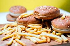 Burger buns with french fries on wooden background. Tasty burger buns with french fries on a wooden background Royalty Free Stock Photography