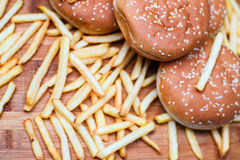Burger buns with french fries on wooden background. Tasty burger buns with french fries on a wooden background Stock Image