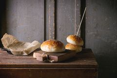 Burger buns. Fresh baked burger buns on small cutting board over wooden table. Dark rustic style stock image