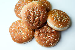 The burger buns on white background. Closeup of tasty burger buns with sesame on a white and yellow background Stock Photos