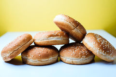 The burger buns on white background. Closeup of tasty burger buns with sesame on a white and yellow background Stock Photography