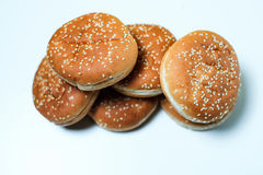 The burger buns on white background. Closeup of tasty burger buns with sesame on a white and yellow background Royalty Free Stock Photography