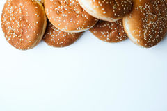 The burger buns on white background. Closeup of tasty burger buns with sesame on a white and yellow background Stock Image