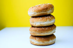The burger buns on white and yellow background. Tasty burger buns with sesame on a white and yellow background Stock Photos