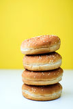 The burger buns on white and yellow background. Tasty burger buns with sesame on a white and yellow background Stock Images