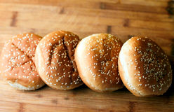 The burger buns on wooden background. Tasty burger buns with sesame on a wooden background Stock Image