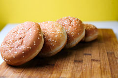The burger buns on wooden background. Tasty burger buns with sesame on a wooden background Royalty Free Stock Image
