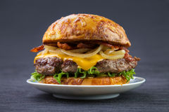 Burger with cheese bun. Cheeseburger with bacon and cooked onion on plate , toasted cheese bun Stock Photo