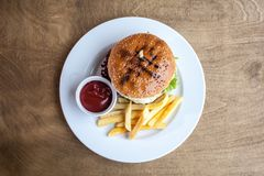 Burger with cheese and a fries and a ketchup. On a plate on a wooden texture ready to eat junk food close up flat layout royalty free stock images