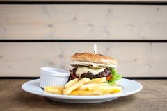 Burger with cheese and a fries and a ketchup. On a plate on a wooden texture ready to eat junk food close up flat layout stock photography