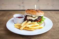 Burger with cheese and a fries and a ketchup. On a plate on a wooden texture ready to eat junk food royalty free stock images