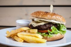Burger with cheese and a fries and a ketchup. On a plate on a wooden texture ready to eat junk food close up royalty free stock photography