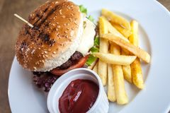 Burger with cheese and a fries and a ketchup. On a plate on a wooden texture ready to eat junk food close up stock photo