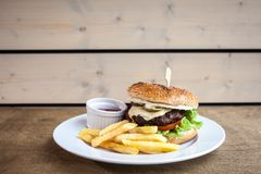 Burger with cheese and a fries and a ketchup. On a plate on a wooden texture ready to eat junk food close up royalty free stock image