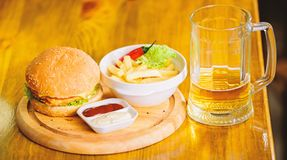 Burger with cheese meat and salad. Pub food and mug of beer. Fast food concept. Burger menu. High calorie snack. Hamburger and french fries and tomato sauce on stock photography