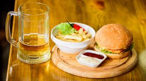 Burger with cheese meat and salad. Pub food and mug of beer. Fast food concept. Burger menu. High calorie snack. Hamburger and french fries and tomato sauce on royalty free stock image