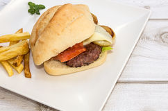 Burger with cheese, tomato, lettuce and chips Stock Images