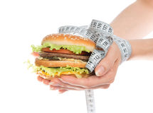 Burger cheeseburger in hands with measure tape Stock Image