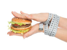Burger cheeseburger in hands with measure tape Stock Photos