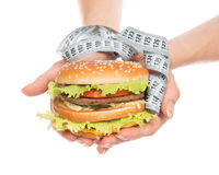 Burger cheeseburger in hands with measure tape Royalty Free Stock Photo