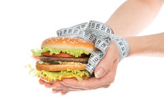 Burger cheeseburger in hands with measure tape Stock Photo