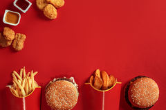 Burger and Chips. Hamburger and french fries in red paper box. Fast food on red background. Stock Photography