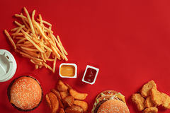 Burger and Chips. Hamburger and french fries in red paper box. Fast food on red background. Stock Photos