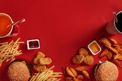 Burger and Chips. Hamburger and french fries in red paper box. Fast food on red background. Stock Image