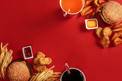 Burger and Chips. Hamburger and french fries in red paper box. Fast food on red background. Stock Images