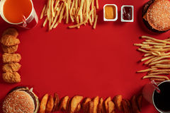 Burger and Chips. Hamburger and french fries in red paper box. Fast food on red background. Royalty Free Stock Photos